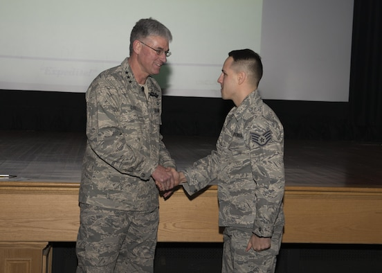 Lt. Gen. Samuel Cox, 18th Air Force commander, shakes the hand of Staff Sgt. Chad Hardesty, 436th Force Support Squadron Airman Leadership School instructor, during an all call March 2, 2017, at Dover Air Force Base, Del. Cox informed Hardesty that he was one of 14 Air Mobility Command members selected to receive a promotion through the Stripes for Exceptional Performers promotion program. The STEP promotion program offers commanders a limited opportunity to immediately promote enlisted members to staff sergeant, technical sergeant or master sergeant. (U.S. Air Force photo by Zachary Cacicia)