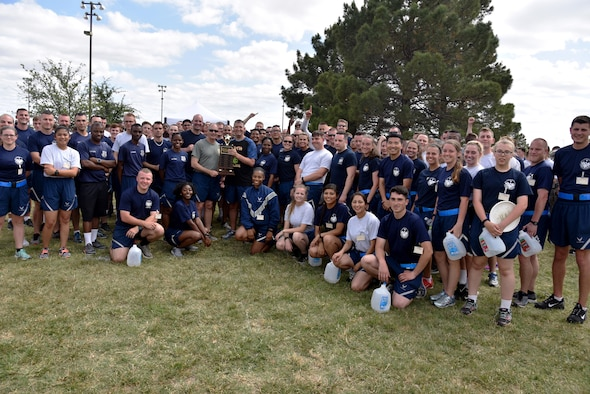 U.S. Air Force Col. Michael Downs, 17th Training Wing Commander, awards the sports day trophy to the 315th Training Squadron near the Mathis Fitness Center on Goodfellow Air Force Base, Texas, April 14, 2017. The 315th TRS placed in the top four teams, then went on to win the winner-take-all tug-of-war competition. (U.S. Air Force photo by Staff Sgt. Joshua Edwards/Released)