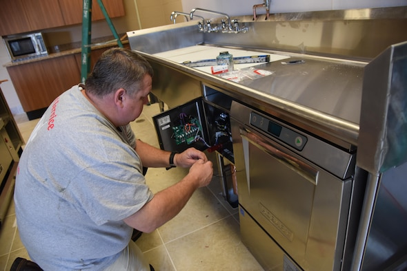 Bo Langford, R and R Food Service installer, connects the solenoid for the garbage disposal at McBride Commons April 11, 2017, on Keesler Air Force Base, Miss. The McBride Commons renovation project will transition the former base library into a common area for those with base access, which includes a children's library, computer stations, engraving, framing, marketing and print shops and a full kitchen. The planned completion date for the nine-month project is May 2017. (U.S. Air Force photo by Kemberly Groue)