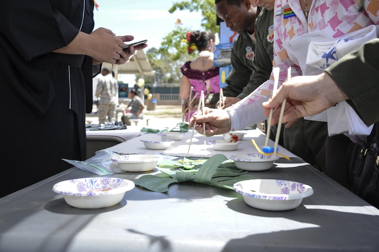 Attendees participate in a timed-contest at the Asian American – Pacific Islander booth during a cultural awareness festival at Davis-Monthan Air Force Base, Ariz., April 17, 2017. The DoD has supported observances through development of local recognition programs and culturally diverse activities since 1968. (U.S. Air Force photo by Airman 1st Class Mya M. Crosby)