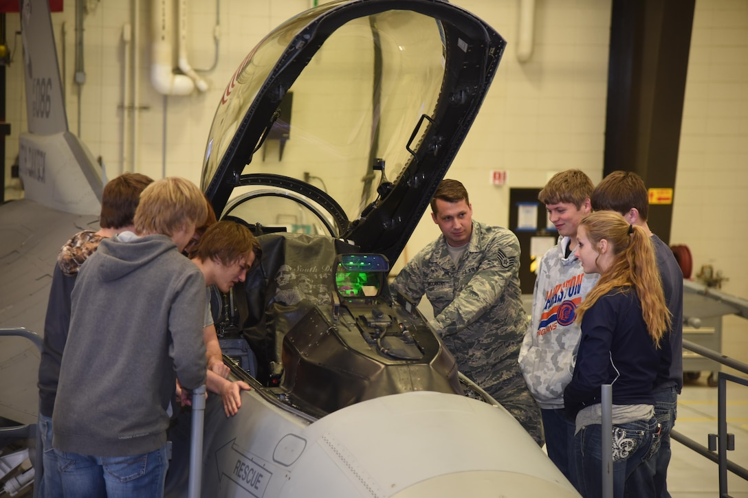 Sioux Falls, S.D. - Staff Sgt. Matt McCarthy, 114th Aircraft Maintenance Squadron electronic systems integrated mechanic, explains the function of an F-16 cockpit to students during the first night flying career day April 13, 2017, Joe Foss Field, S.D. Career day allows students, parents, and others who are interested in the South Dakota Air National Guard to see and learn about the different vocations the 114th Fighter Wing Airmen perform on a daily basis. (U.S. Air National Guard photo by Staff Sgt. Duane Duimstra/Released)