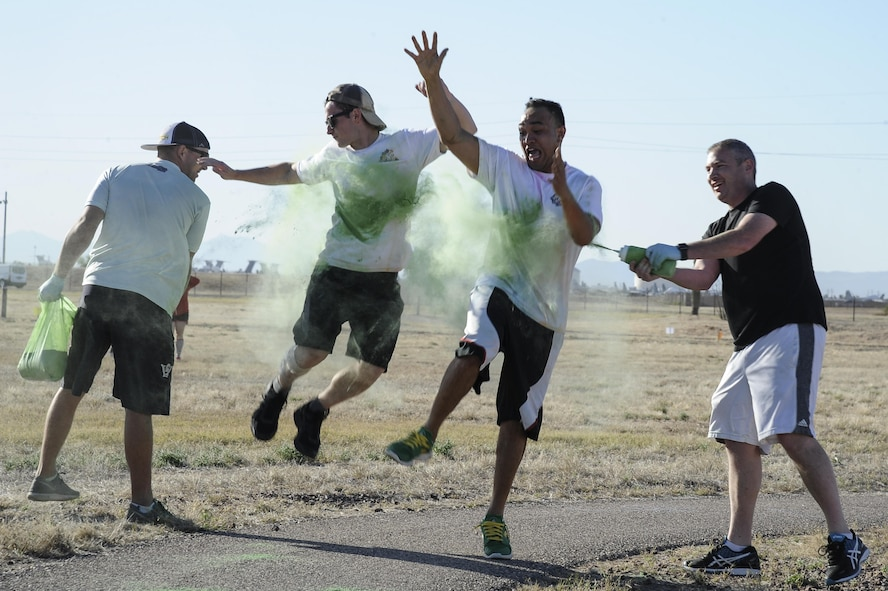 Volunteers spray colored chalk at runners during the 2017 D-M Color Run at Davis-Monthan Air Force Base, Ariz., April 17, 2017. The 5K run kicked off the cultural awareness festival, titled Strengthening Resiliency through Diversity. (U.S. Air Force photo by Airman 1st Class Mya M. Crosby)