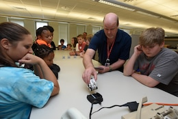 "Ron Douglas, Nashville District Information and Technology chief, uses an interactive toy to explain emerging technologies to kids as part of the district's ""Take Your Kids to Work Day"" activities at the district headquarters in Nashville, Tenn., April 14, 2017."