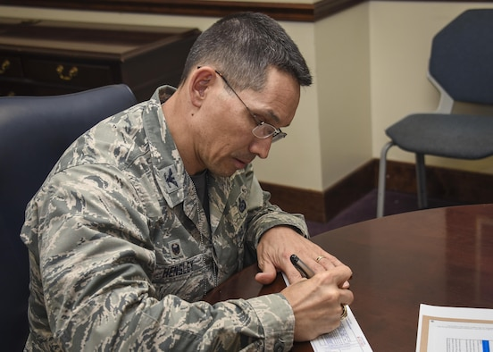 Col. Thomas Hensley, commander of the 70th Intelligence, Surveillance and Reconnaissance Wing, signs an Air Force Assistance Fund pledge form, April 7, 2017 at Fort Meade, Md. The AFAF is an annual effort to raise funds for the charitable affiliates that provide support to the Air Force family in need (active duty, retirees, reservists, guard and dependents, including surviving spouses. The charitable affiliate organizations provide support in an emergency, with educational needs, or a secure retirement home for widows or widowers of Air Force members in need of financial assistance. (U.S. Air Force photo/Staff Sgt. AJ Hyatt)
