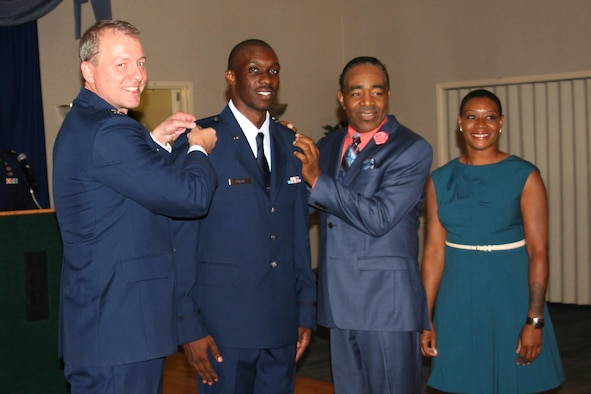 Second Lt. D'Anthony Harris, 413th Aeromedical Staging Squadron medical readiness officer, receives his rank insignia from Col. John Gillespie, former 413th ASTS commander, Pastor Carlton Stephens, and his sister, Khammica Robinson, during a ceremony last year. (Courtesy photo)