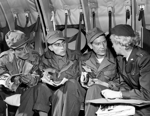 Aboard a C-124 en route to Japan from Korea, three former prisoners of war recently repatriated in the UN POW exchange, Pedro A. Herrera of Albuquerque, New Mexico, Charles Sacco of Loraine, Ohio, and William G. Moreland of Atlanta, Georgia, chat with flight nurse Capt. Dorothy C. Roche of South Acton, Massachusetts.