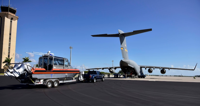 Members of Coast Guard Maritime Safety and Security Team Miami prepare load a small boat onto an Air Force C-17 in Homestead, Florida, on Mar. 8, 2017. An Air Force C-17 airplane transported two MSST boats from Homestead to Tampa to highlight the value of using joint service airlift operations to transport assets over large distances as part of exercise Patriot Sands.