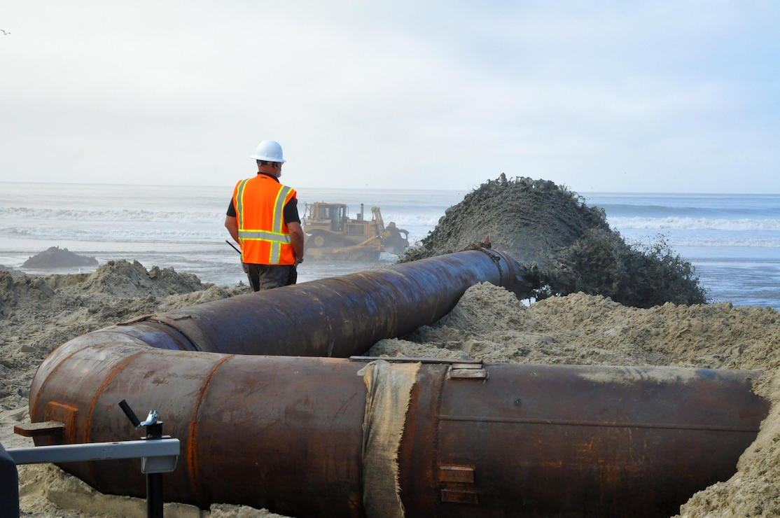 Manson Construction Company pumps material from the Oceanside Harbor entrance channel onto the beach just south of the San Luis Rey River. As the beach widens and provides the route for additional pumping, construction workers will add more sections to the pipe to eventually reach the Oceanside Pier.