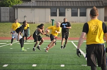 Reserve Gold quarterback Jeff Inferrere sprints to evade three 72nd Security Forces Squadron defenders in the April 4 intramural flag football game near the dorms. Gold won 22-6. (Air Force photo by John Parker)