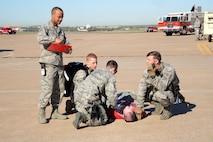 Medics with the 72nd Medical Group, along with members of the 72nd Security Forces Squadron, help stabilize a moulage victim during the April 6 emergency response exercise. About 150 volunteers helped bring to life a more realistic-feeling exercise, which enabled first responders to know how to better react in real world situations. (Air Force photo by Kelly White)