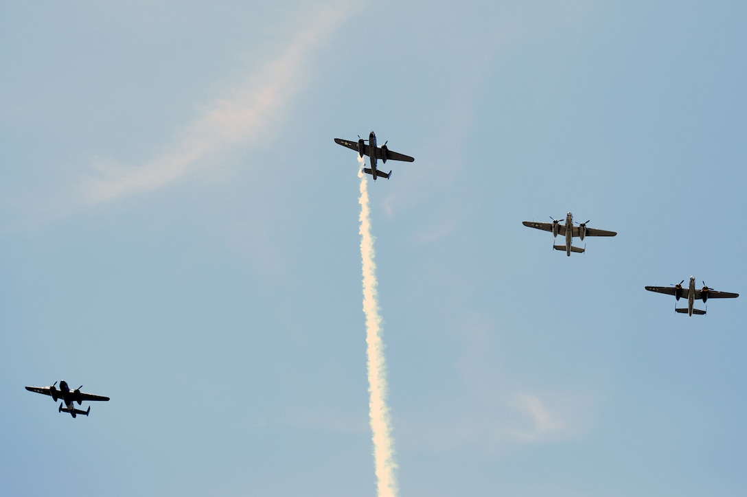 """Four B-25 bombers fly the """"Missing Man"""" formation over the Memorial Service honoring the 75th anniversary of the Doolittle Japan Raid on April 18, 1942. The memorial service, held at the National Museum of the United States Air Force April 18, 2017, included two B-25 fly-overs. The first was a typical bomber staggered formation, and included 11 aircraft. The second was the Missing Man formation and honored the 79 members of the original Raiders who have passed. The last living Raider, Lt. Col. Richard Cole, was a participant in the memorial ceremony.  (U.S. Air Force photo/Wesley Farnsworth)"""