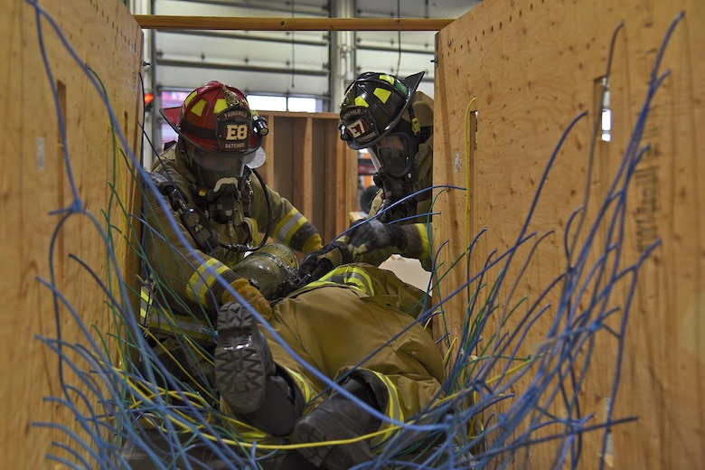 92nd Civil Engineer Squadron firefighters help a fellow firefighter escape the entanglement trainer Mar. 29, 2017, at Fairchild Air Force Base, Washington. The entanglement trainer is one of the various obstacles used during the Rapid Intervention Crew training to simulate a structure fire. (U.S. Air Force photo/Senior Airman Mackenzie Richardson)