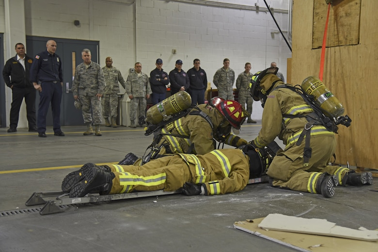 92nd Civil Engineer Squadron firefighters work together to rescue a downed firefighter during a demonstration of their Rapid Intervention Crew training Mar. 29, 2017, at Fairchild Air Force Base, Washington. The demonstration was part of a visit by Col. James Kossler, Air Force Installation and Mission Support Center Detachment 9 commander, to show the progression and implementation of RIC training. (U.S. Air Force photo/Senior Airman Mackenzie Richardson)