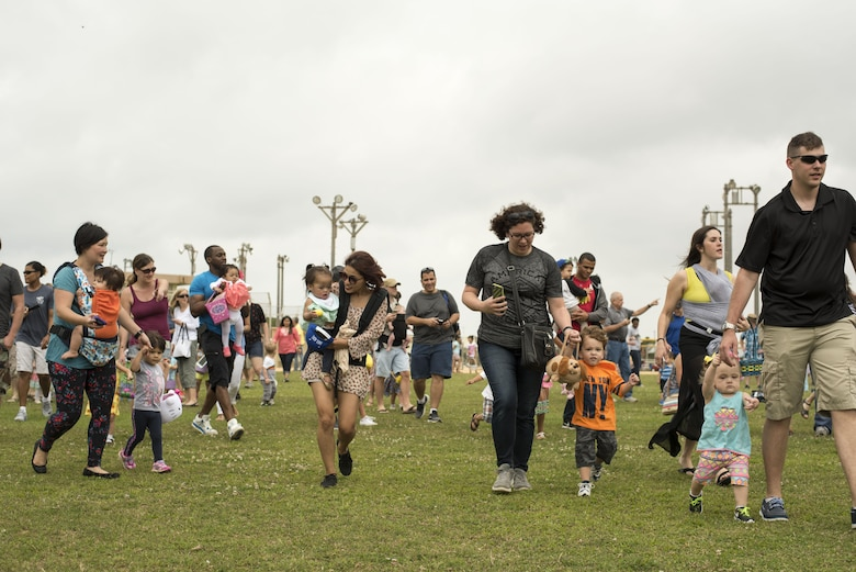 "Families race to collect Easter eggs scattered on the Four Diamonds softball field April 15, 2017, at Kadena Air Base, Japan. The Eggsplosion, an annual event hosted by the 18th Force Support Squadron, featured egg hunts for different age groups and also hosted a ""Kiddie Land"" area with amusement rides designed for children. (U.S. Air Force photo by Senior Airman Omari Bernard/Released)"