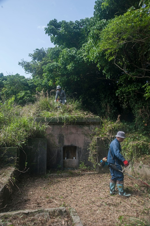 Local Okinawan men remove overgrown vegetation from a family tomb April 9, 2017, at Kadena Air Base, Japan. Members of the communities across the island of Okinawa visit the tombs of their ancestors during the month of April. Airmen from the 18th Munitions Squadron serve as escorts for the families whose ancestral tombs are within the defined area of Kadena. (U.S. Air Force photo by Airman 1st Class Quay Drawdy)