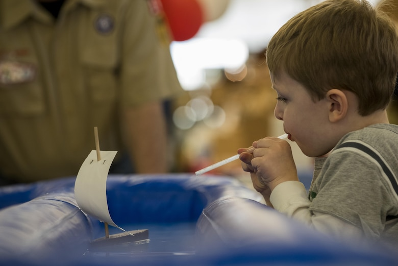 A Spangdahlem child uses a straw to propel a toy boat during the fourth annual Spring Fling event in the Base Exchange at Spangdahlem Air Base, Germany, April 14, 2017. The event was held to bring awareness to the Exceptional Family Member Program and included various activities for children such as face painting, craft making, a bouncing castle and boat races. (U.S. Air Force photo by Airman 1st Class Preston Cherry)