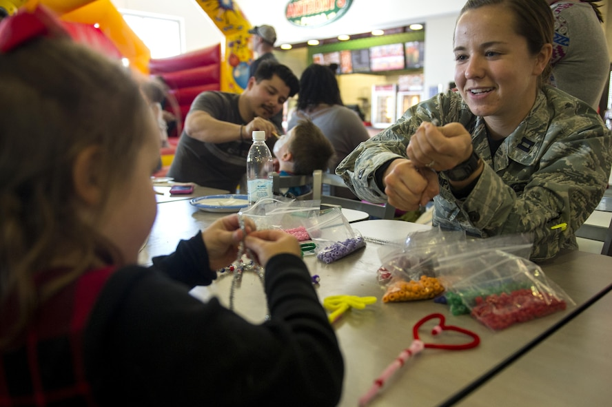 Capt. Katelin Shipp, 52nd Force Support Squadron protocol officer, demonstrates how to make a decorative star during the fourth annual Spring Fling event in the Base Exchange at Spangdahlem Air Base, Germany, April 14, 2017. The event was held to bring awareness to the Exceptional Family Member Program and included various activities for children such as face painting, craft making, a bouncing castle and boat races. (U.S. Air Force photo by Airman 1st Class Preston Cherry)