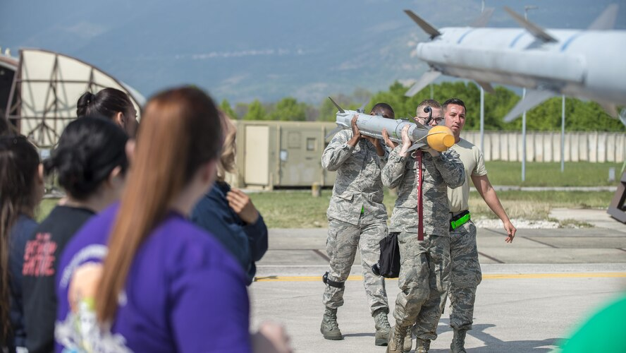 31st Aircraft Maintenance Squadron weapons loader crewmembers, demonstrate how to load munitions during a Spouses' Appreciation Day event at Aviano Air Base, Italy, April 12, 2017. Throughout the day, spouses performed an intake and exhaust check, operated a targeting pod, helped load munitions, completed a wire repair, and even swapped out an F-16 Fighting Falcon tire. (U.S. Air Force photo by Senior Airman Cory W. Bush)