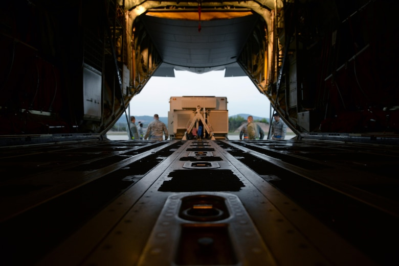 Airmen from the 1st Combat Communication Squadron along with 37th Airlift Squadron load a Tactical Air Navigation system onto a C-130 aircraft April 15, on Ramstein Air Base, Germany. The TACAN works by sending and receiving signals from aircraft notifying them of their bearing and distance in relation to the base. (U.S. Air Force photo by Airman 1st Class D. Blake Browning)