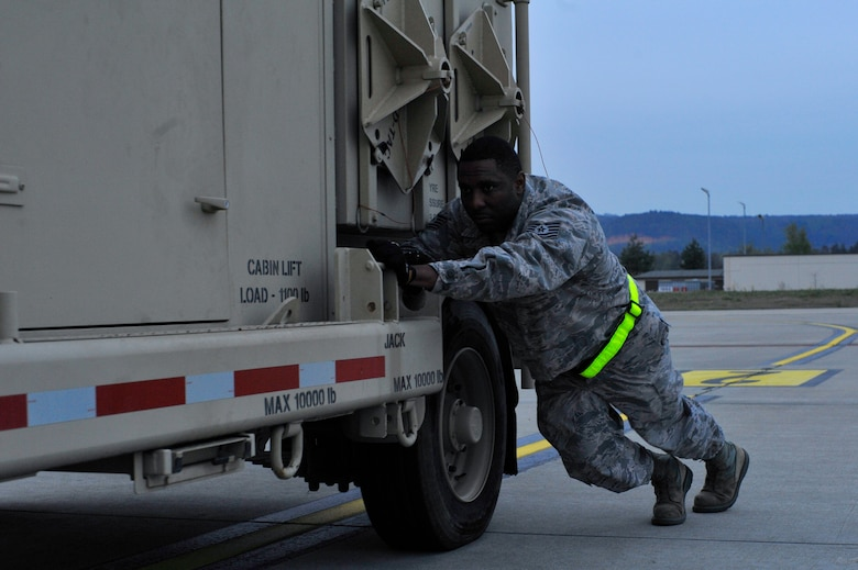 Tech. Sgt. Franklin Wilson, 1st Combat Communication Squadron non-commissioned officer in charge of deployable air traffic control and landing systems, pushes the Tactical Air Navigation system to the back of the C-130 aircraft April 15, on Ramstein Air Base, Germany. The TACAN is scheduled to arrive in Romania, to support the 122nd expeditionary fighter squadron. (U.S. Air Force photo by Airman 1st Class D. Blake Browning)