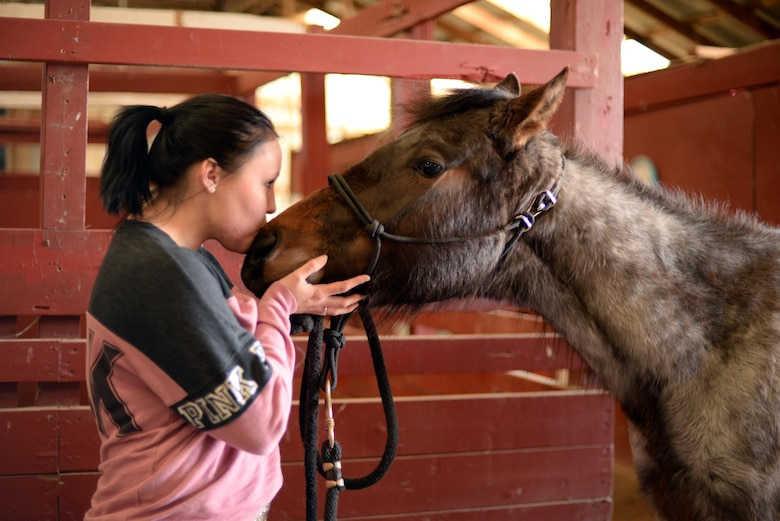 Bobbie Scheffler, 5th Force Support Squadron missile chef, kisses her two-year-old horse Athena on the nose at the Dufresne Riding Club Stables at Minot Air Force Base, N.D., April 11, 2017. One of Dufresne Riding Club goals is to raise the moral of those on base by giving them a place to relax and feel at ease. (U.S. Air Force photo/Airman 1st Class Austin M. Thomas)
