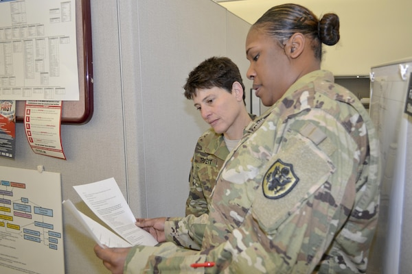 Army Maj. Kellie TRriplett, a veterinary liaison officer, and Army chief Warrant Officer 3 Jemme Neal, consumer safety officer, review an ALFOODACT message. Triplett and Neal are part of the Subsistence Food Safety Office at DLA Troop Support, which oversees food safety for the military.