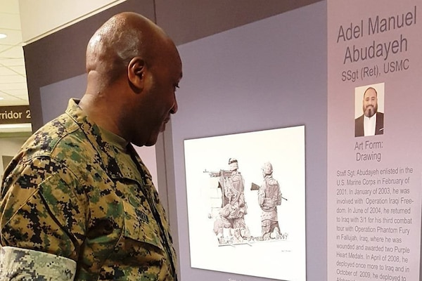 Sgt. Maj. of the Marine Corps Ronald L. Green reads the biography of retired Marine Staff Sgt. Adel Abudayeh whose artwork is on display at the Pentagon Patriotic Art Program: Wounded Warrior Healing Arts exhibit, April 12, 2017. Marine Corps photo by Victoria Long