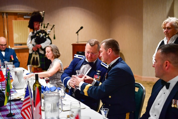 Col. Gregor J. Leist, Western Air Defense Sector commander, passes the port to Canadian Brig. Gen. David Cochrane, 2nd Canadian Air Division commander, during the annual Canadian Mess Dinner marking the 93rd anniversary of the formation of the Royal Canadian Air Force.  The manner in which the port is passed is military service specific.  In case of the Air Force, the port never touches the table to symbolize flight.  The port is used for all of the official toasts during the Mess Dinner.  (U.S. Air Force photo by Kimberly D. Burke)