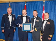 During the annual WADS Canadian Mess Dinner, Canadian Brig. Gen. David Cochrane (middle-right), 2nd Canadian Air Division commander, presents Col. Gregor J. Leist (middle-left), Western Air Defense Sector commander, with the 2nd CAD Commander's Unit Commendation.  Canadian Lt. Col. Matt Wappler (right), WADS Canadian Detachment commander, nominated WADS for consistently providing critical live and virtual training to Canadian aerospace controllers from the 51 Aerospace Control and Warning (Operational Training) Squadron located at North Bay, Ontario. (Courtesy photo by Conrad Neumann III)