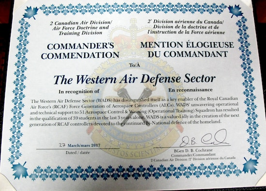 The 2nd Canadian Air Division Commander's Unit Commendation citiation is presented to the Western Air Defense Sector during the Canadian Mess Dinner April 7 for providing critical live and virtual training to Canadian aerospace controllers from the 51 Aerospace Control and Warning (Operational Training) Squadron from North Bay, Ontario.