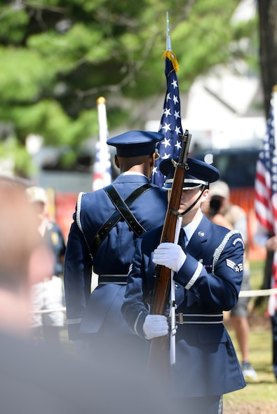 Senior Airman Roman Vizone, ceremonial guardsman with the Wright-Patterson Air Force Base Honor Guard, stands at port arms as Airman 1st Class Izan Velazquez places the American Flag in its stand at the 75th Anniversary memorial ceremony of the Doolittle Tokyo Raid, April 18, 2017 at the National Museum of the United States Air Force in Dayton, Ohio. Attending the ceremony was Chief of the Staff of the Air Force, Gen. David L. Goldfein, Lt. Col. (Ret.) Richard E. Cole, the sole surviving member of the Doolittle Raiders, and Jeff Thatcher, the son of Doolittle Raider Staff Sgt. David Thatcher, who passed in June 2016. (U.S. Air Force Photo/Wesley Farnsworth)