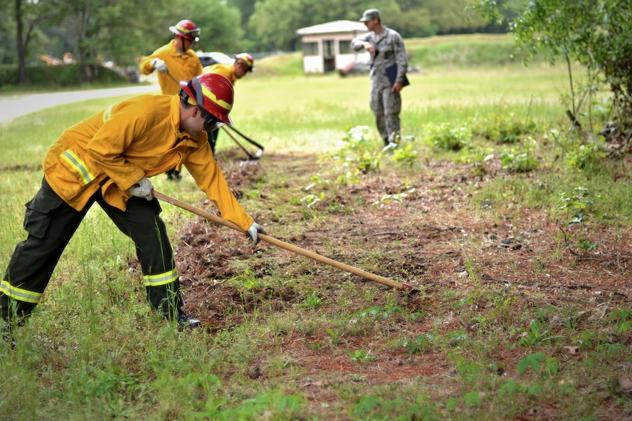 U.S. Airmen assigned to the 20th Civil Engineer Squadron fire department remove ground debris during a simulated wildfire training at Shaw Air Force Base, S.C., April 19, 2017. As part of mandatory certifications, firefighters are required to practice proper wildfire safety procedures to include, protecting people and property in the surrounding area. (U.S. Air Force photo by Airman 1st Class Christopher Maldonado)