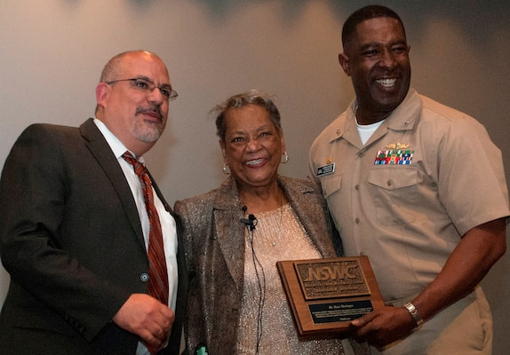 """Naval Surface Warfare Center Dahlgren Division (NSWCDD) leaders present a plaque to Raye Montague in appreciation of her keynote speech at the command sponsored Women's History Month Observance. Montague was the first person to design a U.S. Navy ship - the USS Oliver Hazard Perry (FFG-7) - using a computer, revolutionizing naval ship design. The Navy's """"hidden figure"""" spoke about her life and career experiences, sharing her words of wisdom to all gathered at the Naval Support Facility (base) theater to celebrate the observance. Standing left to right: NSWCDD Technical Director John Fiore; Montague; and NSWCDD Commanding Officer Capt. Godfrey 'Gus' Weekes."""