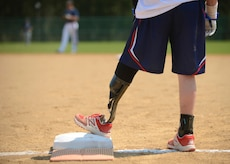 """A Wounded Warrior Amputee Softball Team member stands on first base during the WWAST game against the Newport News police and fire departments in Newport News, Va., April 15, 2017. The members' amputations range from above the knee to below the elbow, and they hope to educate others that """"life without limbs is limitless."""" (U.S. Air Force photo/Airman 1st Class Kaylee Dubois)"""