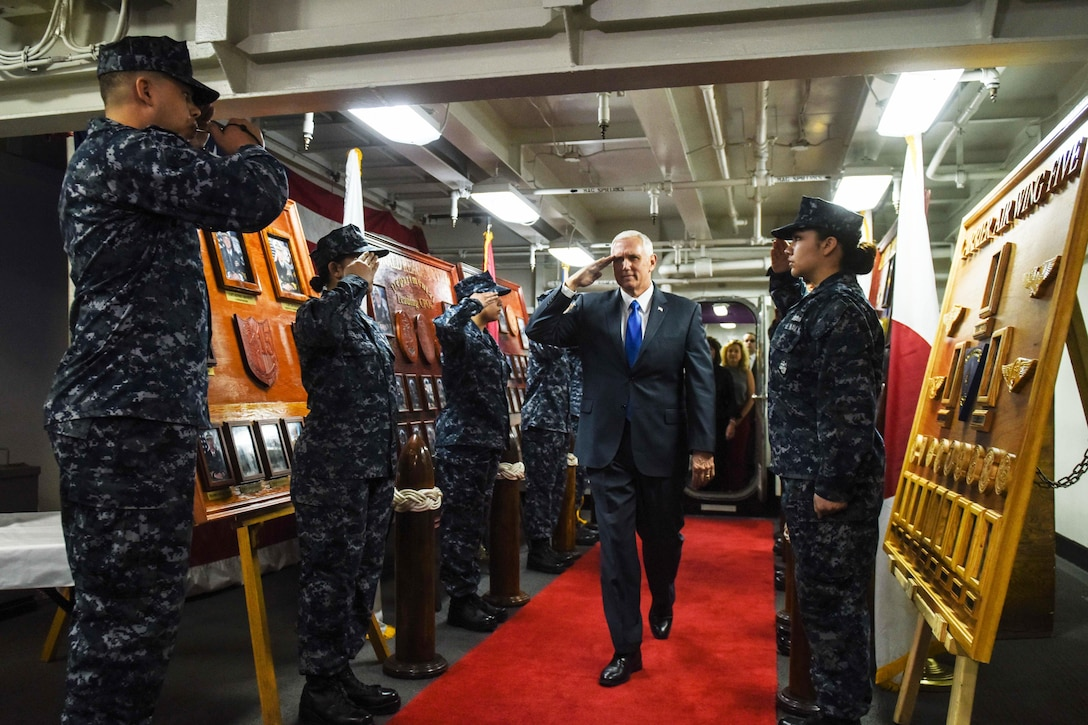 Vice President Mike Pence salutes sailors upon arriving aboard the forward-deployed aircraft carrier USS Ronald Reagan.