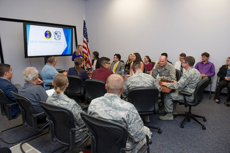 A Lake Nona High School student discusses her findings and results in regards to weather and climatology to members of the 45th Space Wing during a visit April 18, 2017, at Cape Canaveral Air Force Station, Fla. Prior to the school year, William Roeder, 45th Weather Squadron meteorologist, reached out to the high school and introduced them to the project. The project provides students with real-world experience by following a business model of preparation, set-up, and using innovative methods to complete it. (U.S. Air Force photo by Phil Sunkel)
