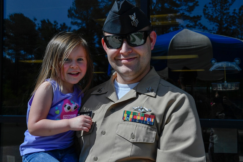Petty Officer 1st. Class Robert Bromley, Naval Nuclear Power Training Command, holds his daughter, Madelynn, at the Joint Base Charleston-Weapons Station Child Development Center, April 13, 2017. April was named Month of the Military Child by former Defense Secretary Casper Weinberger in 1989 to applaud military children for their daily sacrifices and the challenges they have overcome. WS CDC is celebrating Month of the Military Child by hosting Wacky Hat Wednesdays, Purple Up! Fridays and planting gardens with parents and students.