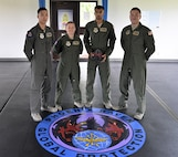 The 60th Security Forces Squadron Phoenix Raven team members Senior Airman Joshua Wolf (left), Tech Sgt. Brooke Williams (center left), Senior Airman Mayursinh Jadeja (center right) and Staff Sgt. Trevor Lopez (right) stand behind the Phoenix Ravens seal April 6 at Travis Air Force Base, California. The Ravens recently completed a unique capstone mission in Africa Feb. 14 through 25. (U.S. Air Force photo / 2nd Lt. Sarah Johnson)