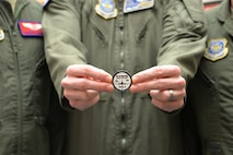 The aircrew who completed the final KC-10 Extender modification flight displays the coin they received to signify the completion of the project April 5 at Travis Air Force Base, California. The 59th and final KC-10 was modified and flown home by the 9th and 6th Air Refueling Squadrons at Travis March 28. (U.S. Air Force photo / 2nd Lt. Sarah Johnson)