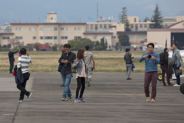Participants walk on the flightline after landing at Yokota Air Base, Japan, during the Kanto Plain Mid-Air Collision Avoidance Conference, April 15, 2017. The conference brought together military and civilian pilots from all over Japan to focus on flight safety and base flight procedures. (U.S. Air Force photo by Yasuo Osakabe)