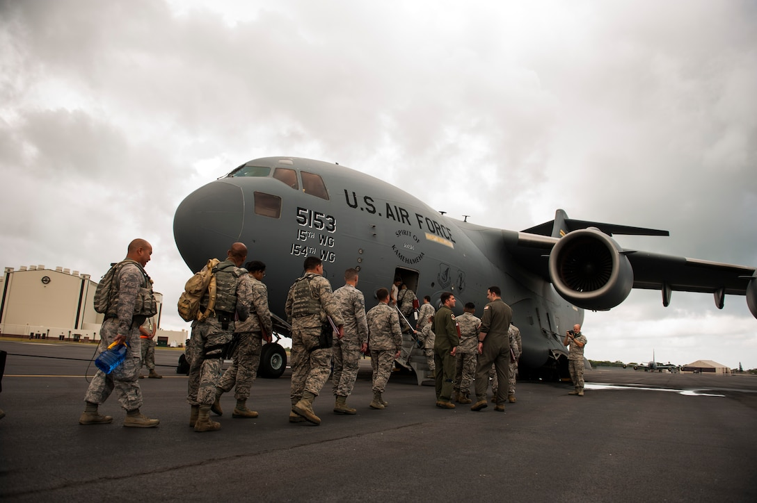 Airmen board a C-17 Globemaster III headed to Wheeler Army Airfield, Hawaii for Exercise TROPIC THUNDER 2017 (XTT17), Joint Base Pearl Harbor-Hickam, Hawaii, April 19, 2017. XTT17 is a two part full spectrum readiness exercise hosted by the 15th Wing to test the individual, organizational and expeditionary readiness of the Airmen stationed at Hickam Field. (U.S. Air Force photo by Tech. Sgt. Heather Redman)