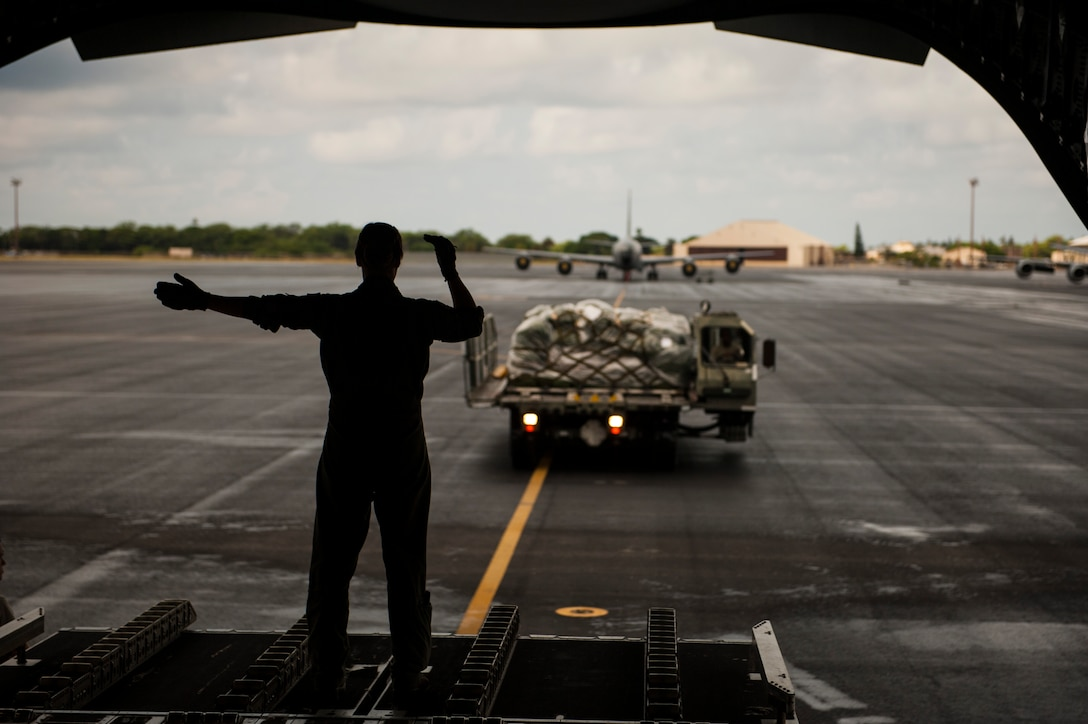 Senior Airman Korina Myers, loadmaster assigned to the 535th Airlift Squadron, directs cargo loading on a C-17 Globemaster III during Exercise TROPIC THUNDER 2017 (XTT17), Joint Base Pearl Harbor-Hickam, Hawaii, April 19, 2017. XTT17 is a two part full spectrum readiness exercise hosted by the 15th Wing to test the individual, organizational and expeditionary readiness of the Airmen stationed at Hickam Field. (U.S. Air Force photo by Tech. Sgt. Heather Redman)