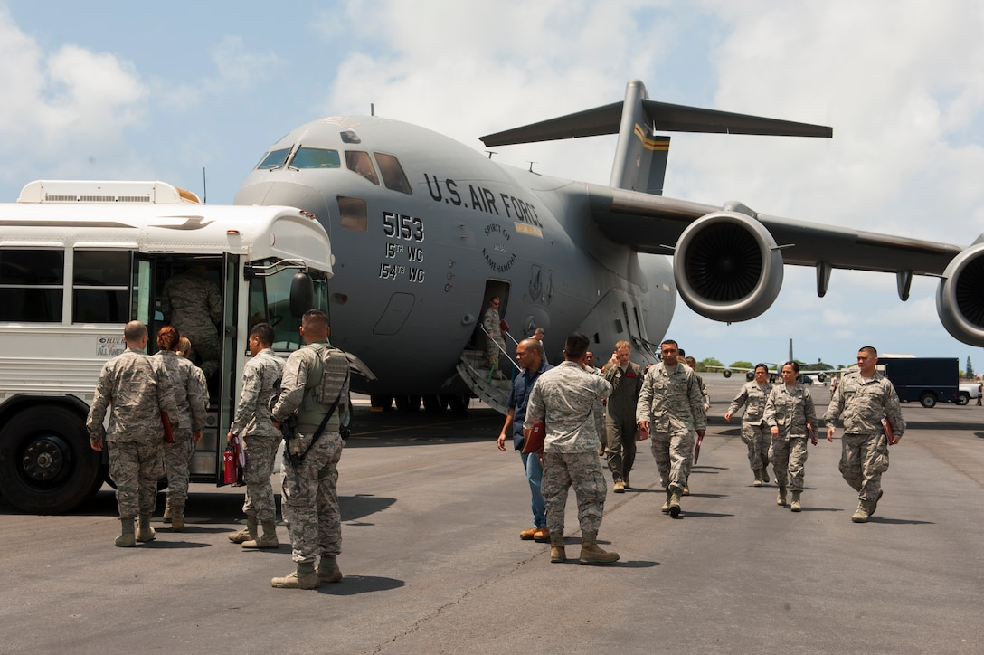 Airmen disembark a C-17 Globemaster III and load onto a bus headed for Wheeler Army Airfield on Joint Base Pearl Harbor-Hickam, Hawaii, April 19, 2017. The C-17 was headed to Wheeler for Exercise TROPIC THUNDER 2017 (XTT17) but was diverted due to weather.  XTT17 is a two part full spectrum readiness exercise hosted by the 15th Wing to test the individual, organizational and expeditionary readiness of the Airmen stationed at Hickam Field. (U.S. Air Force photo by Tech. Sgt. Heather Redman)