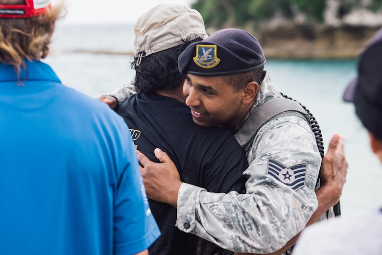 U.S. Air Force Tech. Sgt. Oswaldo Cerrato, 18th Security Forces Squadron flight lead, thanks U.S. Air Force retired Master Sgt. David Lacar for his efforts in the rescue of a dwarf sperm whale April 17, 2017, at Kadena Marina, Japan. Lacar aided in the rescue effort for the whale after Okinawan fishermen spotted the whale and called for help. (U.S. Air Force photo by Senior Airman Omari Bernard/Released)