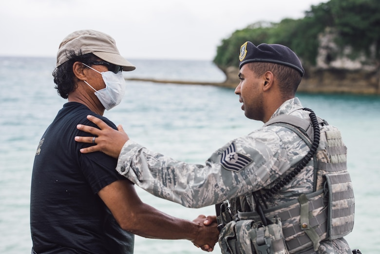 U.S. Air Force Tech. Sgt. Oswaldo Cerrato, 18th Security Forces Squadron flight lead, thanks U.S. Air Force retired Master Sgt. David Lacar for his efforts in the rescue of a dwarf sperm whale April 17, 2017, at Kadena Marina, Japan. Lacar was relieved by 18th Force Support Squadron divers after supporting the injured dwarf sperm whale for more than two hours. (U.S. Air Force photo by Senior Airman Omari Bernard/Released)