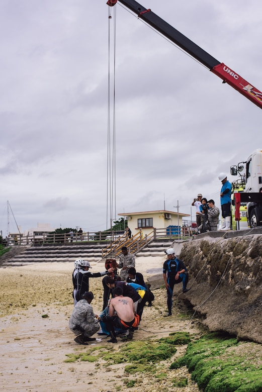 A makeshift rescue team of Okinawan veterinarians, and personnel from the 18th Security Forces Squadron and 18th Force Support Squadron secure an injured dwarf sperm whale to a crane April 17, 2017, at Kadena Marina, Japan. The team worked together to transport the whale to the Charumi Aquarium for medical care. (U.S. Air Force photo by Senior Airman Omari Bernard/Released)