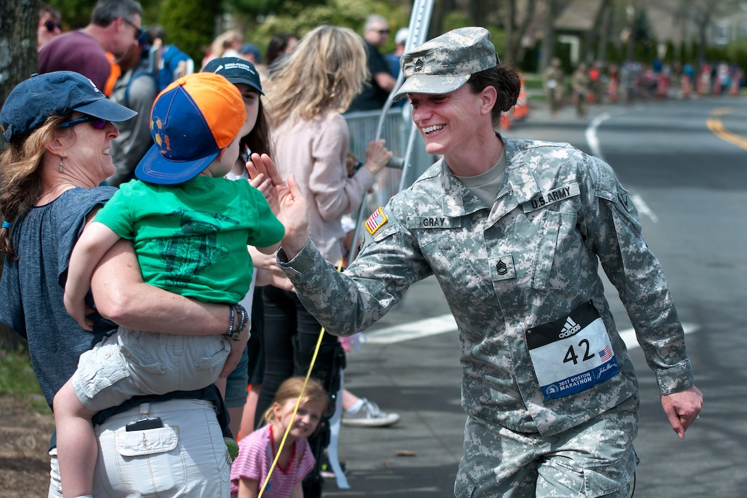 A Massachusetts Army National Guardsman high-fives a child while participating in the 121st Boston Marathon in Newton, Mass., April 17, 2017. Dozens of Massachusetts National Guardsmen participated in the marathon as well as assisted local law enforcement with security.  Army National Guard photo by Staff Sgt. Evan Lane