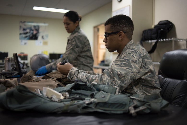 U.S. Air Force Airman Nigel Simpson, 18th Operations Support Squadron aircrew flight equipment technician assigned to the 44th Fighter Squadron, services a survival vest April 18, 2017, at Kadena Air Base, Japan. The AFE shop oversees pilots' item serviceability and restocks their uniform with supplies like water and food if needed. (U.S. Air Force photo by Senior Airman John Linzmeier)
