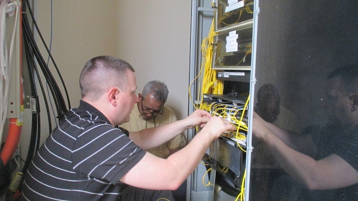 Members of the 38th Cyberspace Engineering Installation Group work together to identify wire locations on a core node March 28, 2017, at Kadena Air Base, Japan. Reducing the number of routers was the primary focus of the 38th CEIG during their month-long temporary assignment to Kadena. The reduction is estimated to save the 18th Communications Squadron more than 100 man hours of maintenance each year. (Courtesy photo)