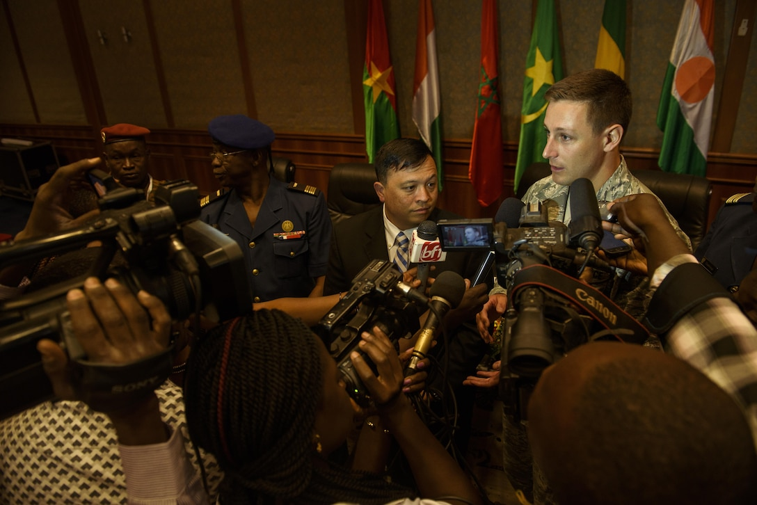 U.S. Air Force Capt. Thomas Bowen, right, translates for Col. Ric Trimillos, center, U.S. Air Forces in Europe-Air Forces Africa division chief of international affairs, during a press conference at opening ceremony of the African Partnership Flight in Ouagadougou, Burkina Faso, April 18, 2017. APF in Burkina Faso hosted participants from Chad, Mali, Mauritania, Niger, Cote d'Ivoire and Morocco to help strengthen relationships and share best practices.